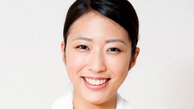 headshot of young woman on gray background