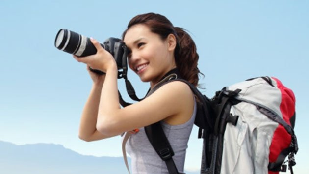 Woman standing on mountain top with camera