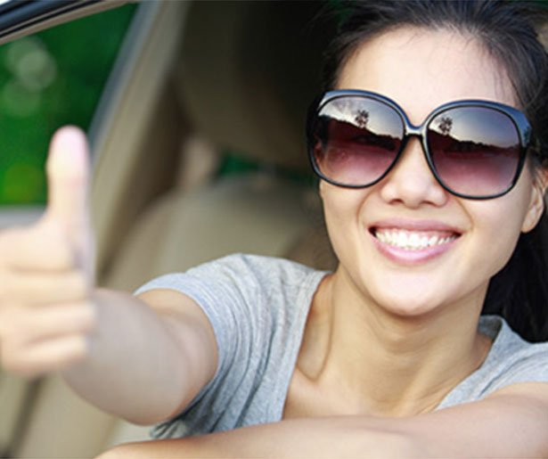 woman in sunglasses giving thumbs up